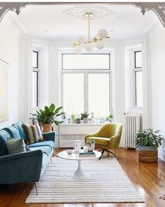 The asymmetrical styling of the room helps add to its openness. Where the dark blue couch adds heaviness, there are smaller items in the other side to balance it out (the armchair, the plant, the corner of a rug peeking at the corner).  Even the light fixture adds some diagonal interest directing the eye back to the couch.