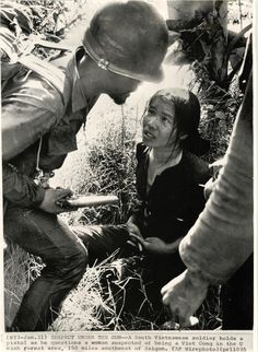 SUSPECT UNDER THE GUN - A South Vietnamese soldier holds a pistol as he questions a woman suspected of being a Viet Cong in the U Minh forest area, 150 miles southwest of Saigon.