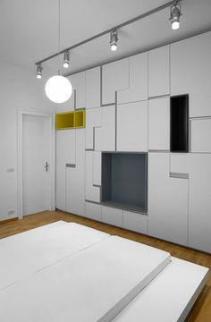 Inspiration wise, there are a few retail options out there that offer you similar options to divide a large space while offering hidden storage: the IKEA Pax Wardrobe can be used as a partition and storage unit, and AT reader Alex showed us how to use as-is pieces from IKEA to create an expansive room divider with a less stark effect.