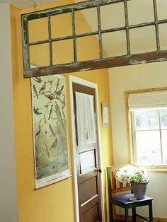 A rustic multi-paneled window makes a stylish substitute for a transom in the passageway between the entry hall and the living room.