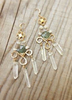 """These earrings feature beautiful crystal quartz points dangled on a handmade hammered gold fill loop. Tiny moonstones  link to the top with a gold vermeil connector piece at the very top and a green moss amethyst at the very center. They measure approx. 3"""" long and are very light weight. Ear wires are 14k gold fill."""