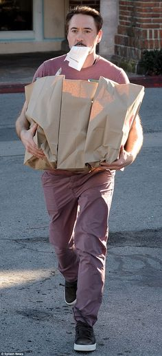 Biting off more than you can chew? Robert Downey Jr. emerged from CVS in Malibu with his receipt in his mouth and his arms laden with shopping bags on Saturday