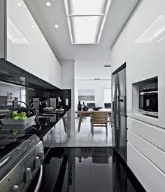 Cobertura em Belo Horizonte / Pedro Lázaro / O brilho dá a palavra de ordem nos revestimentos novos na cozinha, do granito preto absoluto do piso à laca da marcenaria.