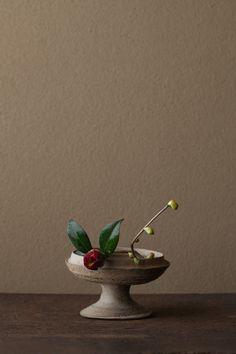 2012年4月10日(火)     秋から春へ、椿の赤はだんだん濃くなります。黒椿は思いの深い花。   花=土佐水木(トサミズキ)、黒藪椿(クロヤブツバキ)   器=須恵器高杯(古墳時代)