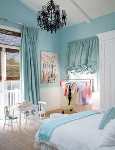 Windsor Smith - gorgeous turquoise blue girl's bedroom design with turquoise blue walls paint color, chair rail, blue silk pinch pleat drapes, bamboo roman shades, jute rug, glossy black chandelier with plaid shades and blue pillow & throw.