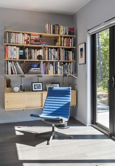 The interiors are furnished with midcentury piecesincluding this vintage Eames Aluminum Group chair. Fireplace Bookcase, Bookcase Wall, Bookshelves, Prefab Homes, Modular Homes, Modern Chairs, Midcentury Modern, Timber Deck, Minimalist Kitchen