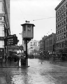 """THEN: Looking west on Pike Street, we see Seattle's first traffic tower, which went into service July 20, 1925. Among the many businesses in the area is the Fahey-Brockman men's clothing store, where one may """"buy upstairs and save $10.00."""" (Courtesy)"""