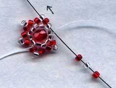 Star Ornament  Pick up your 3 beads, skip next bead in ring, and go through next like before, but then also go up through the first red and silver bead from the last row, so that you are coming out of the 1st point you made.