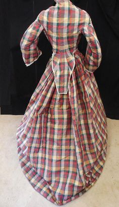 "Darling Orig Victorian 1860 Civil War Plaid Silk Taffeta Hoop Pagoda Dress Gown | eBay seller bydenise; 1850s/60s; 2-piece, bodice lined, piping at collar & armsyces; silk ribbon & net trim on sleeves; front button closure; cartridge pleating, 5.5"" buckram at hem, wool binding on hem; minimal underarm spots, some light water marks, some slits, period mends; shown on mannequin with 32/34"" bust; skirt waist: 26""; skirt length: 41-53"".  [Perhaps, later 1860s when elliptical hoops were worn.]"