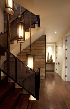 A central stairway wall created with horizontal wood board paneling is lit by custom rope-hung lanterns.
