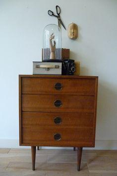 teak dresser, wall cabinet, 60\s.  Jaren 60 ladenkast. Solide kastje van teakhout in een mooie warme kleur. Vier laden met ronde messing greepjes. De bovenste la heeft een vakverdeling. De ranke poten zijn afgewerkt met messing vloerdoppen.  Geen noemenswaardige beschadigingen, in prima vintage staat.  Afmetingen: b 59 x h 80 x d 44 cm.  Prijs: € 125,-
