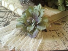 A Neo-Victorian hair clip with a sage/purple flower, feather and cream lace.