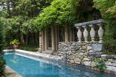 At garden designer Michael Trapp's Connecticut home, a slender pool is tucked between cracked curbing and finely sculpted shrubs. A poolside grotto, accessed by ducking under flourishing wisteria, is a folly used for entertaining.