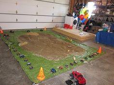 Activity: green tarp, sand, woo pieces, traps, cars, trucks, orange cones