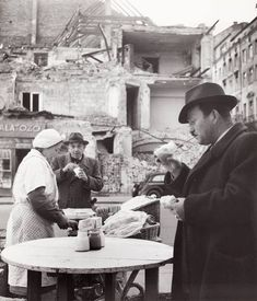 """1948. Budapest, """"Élelmiszer árusítás kosárból, egy hotel romjai közelében"""" (Robert Capa)"""