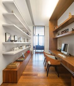 This home office has plenty of shelves for storage and a built-in desk ready for work.