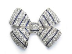 An Art Deco sapphire and diamond bow brooch, set with old-cut diamonds and highlighted with rows of calibre cut sapphires, mounted in platinum.