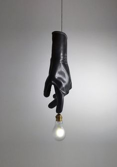 ingo maurer's luzy lights illuminate the fingertips of plastic gloves