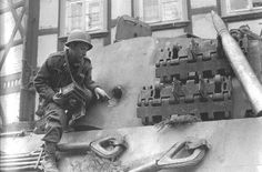 Un photographe militaire américain observe le trou d'entrée provoqué par un projectile de Bazooka qui a pénétré du côté droit de la tourelle (armure de 80 mm d'épaisseur) de ce Tiger II.