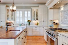 I'm loving this white kitchen. Double stacked floor to ceiling cabinets around sink area. Butcher block island and - - -ooooh - - -the RANGE! I would replace the chandelier with a crystal one.