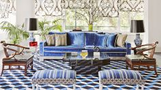 This vibrant living room has patterned carpets, striped ottoman stools, a blue velvet couch, wooden chairs, patterned curtains, matching lamps and potted plants.