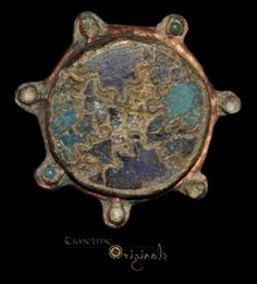 Copper-alloy and enamel, 5.31 grams, 25.32 mm. Circa 10th-11th century AD. An Anglo-Scandinavian disc brooch comprising a central enamel discsurrounded by seven radiating knops filled with enamel cabochons (three remaining). The central panel is a dark blue enamel background with an inset radiating cloison design in black and turquoise enamel. The pin-lug and attachment point for the catchplate are in place on the reverse.  Provenance: from an old English collection, found East Anglia.