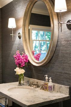 A silver oval mirror is mounted to a wall covered in gray raffia wallpaper between Thomas O'Brien Bryant Sconces fixed above a marble top nickel washstand finished with round sink and polished nickel cross handle faucet.