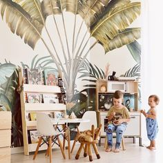 Imagine you're in a rainforest. No, wait a beach lined with palm trees! We adore this kid's interior by combining natural wood, including the Tidy Books kid's bookcase with lush wallpaper Jungle Bedroom, Baby Bedroom, Nursery Room, Boy Room, Kids Bedroom, Chambre Nolan, Tidy Books, Tropical Wallpaper, Wallpaper Jungle