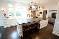 """Island design with spindles and seating on the side. """"The kitchen is a mix of white marble countertops and black honed granite.""""- Munger Interiors"""