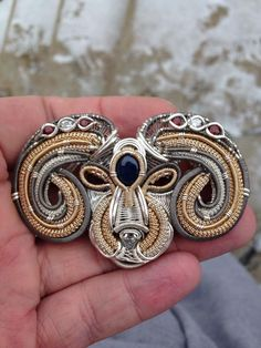 The Ram: Contains 6x garnets 3x diamonds 1x star sapphire. Wrapped in titanium, 14/20 gold filled. And .925/.999 silver, by Zach Welty