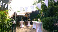 www.trouwenineigentuin.nl Statafels versiert met linten in de kleuren roze, wit en licht groen.
