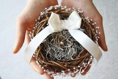 This ring bearer pillow, rustic nest wedding ring box, vegan pearl twig and moss nest ring pillow PUCK contrasts the earthy charm of the twig and vines nest with delicate and ethereal sprays of vegan pearls. PUCK features a soft pillow of spanish moss and a high quality ivory ribbon with a double bow. On your wedding day, your rings will be surrounded by the beauty of vegan pearls, rustic twigs and moss before the