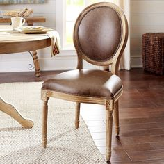 The aristocratic Eliane is a direct descendant of Louis XVI's classic dining chair. Crafted of solid European oak, it features the same iconic oval back, tight, raised seat, corner medallion molding and turned legs as its regal ancestor. Hand-upholstered faux leather and a refined whitewash finish complete the family resemblance. All for <i>beaucoup</i> francs less than the original.