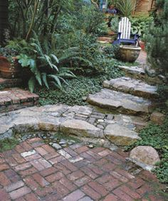 Brick steps line the house and lower courtyard. Grade changes signal you're moving from one place to another. Although the spaces are similar, the narrow passageway divides them.