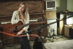 Posing with a guitar, Camille Rowe wears bow-printed blouse and velvet pants