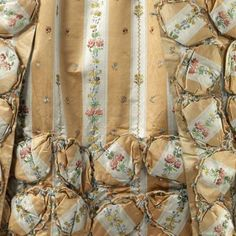 Detail trimming, robe à la francaise, probably France, c. 1770. Yellow and white striped silk, embroidered with flower sprays and a vertical pattern of floral bouquets, lined with multicoloured chiné la branche, fabric trimming.