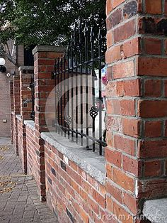 Brick and wrought-iron fence decorated with arrowheads on top.