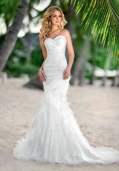This designer mermaid silhouette wedding gown boasts a sweetheart neckline and is beautifully crafted with Soft Organza rouching and vertical tiers. Beaded lace appliques add subtle sparkle