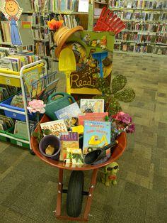 Dig Into Reading Summer Reading Program display Lake Benton Library. Books and garden tools in a Wheelbarrow plants bulletin board