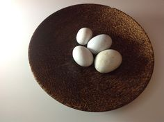 A wooden bowl with white stones