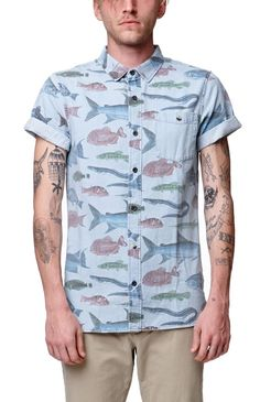 PacSun presents the Modern Amusement Tropical Fish Short Sleeve Denim Shirt for men. This unique men's button up shirt has a blue denim body and a multi color fish print throughout.	Multi color fish print button up shirt	Chest pocket	Medium spread collar	Button front	Short sleeves	Straight yoke	Regular fit	Machine washable	100% cotton	Imported