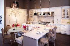 gray L-shaped island paired with a white counter fitted with a farm sink and gooseneck faucet adjacent to a pair of French cafe barstools with a built-in banquette
