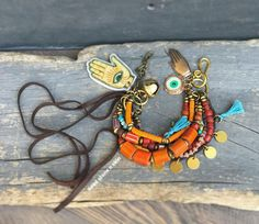 I made this seven strands rustic bracelet with trade beads, seed beads, brass spacers, vintage orange Nepal beads, chevron beads, pressed turquoise, Czech glass beads, one strand is made of soft braided leather. Brass coins are attached to decorate the leather. An evil eye and a hand amulet I have designed myself casted in raw brass and finished by hand, three tiny handmade tassels, a large brass bell and three leather leather straps hanging freely. The brass hook clasp is handmade. The…