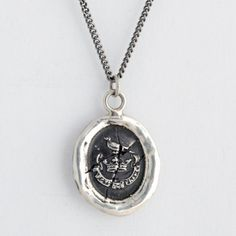 The raven is symbolic of hope and was believed to have keen vision that pierced through all darkness. The Latin inscription on this handcrafted talisman necklace reads Flecti Non Frangi: To Be Bent Not Broken, referring to someone who can endure hardship but continue to stay true to themselves.     Each Pyrrha talisman is cast in reclaimed sterling silver or bronze from a 19th century wax seal and is handcrafted in Vancouver, Canada.
