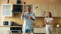Attractive loving couple having fun in the kitchen. Handsome man juggle with apples to impress his girlfriend. Food