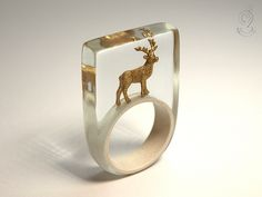 Wood ease – Funny deer ring with a golden deer on a white ring made of resin   ///// © Isabell Kiefhaber www.geschmeideunterteck.de