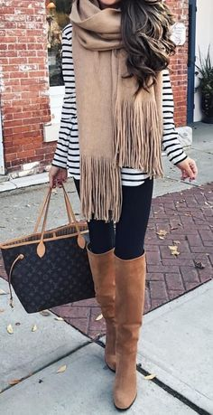 Woman on the street wearing black leggings, striped top, beige scarf, Louis Vuitton handbag and brown boots