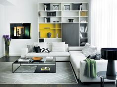 The bookcase from Molteni & C camouflages  a wall vent. Sectional seating and side table are from Molteni & C; the table lamp, from B&B Italia.