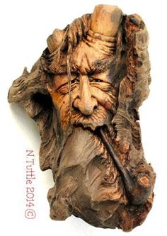 """""""Smoldering Cogitations""""   This smoking sorcerer measures 6 inches   tall and 3¾ inches across his widest point.   I carved his face into the larger, main knot   within this piece of driftwood and carved the   smaller knots to become his pipe and """"horns"""".   Signed and dated:  N. Tuttle 5/15/14"""