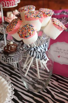 marshmallow dipped in frosting with sprinkles on cookie sticks.